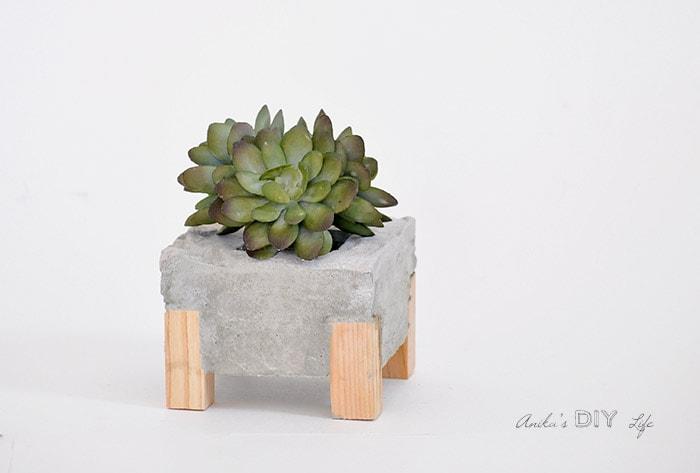 Plantador de concreto com pés de madeira